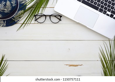 Office table desk, Flat lay, top view. Palm branches laptop keyboard and summer hat. Frame with copy space. Mock up template
