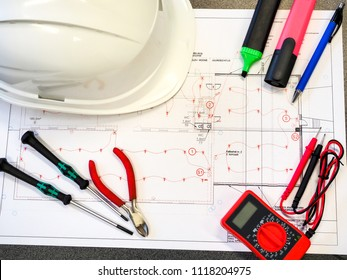 Office table or desk with the project drawings of the security or fire alarm system, a protective helmet, tools, a multimeter and markers.