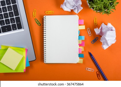Office table desk with set of colorful supplies, white blank note pad, cup, pen, pc, crumpled paper, flower on orange background. Top view and copy space for text