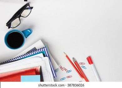 Office table desk with set of colorful supplies, white blank note pad, cup, pen, pc, crumpled paper, flower on white background. Top view and copy space for text