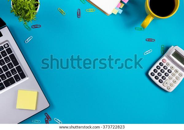Офисный стол с набором красочных принадлежностей, белый пустой блокнот, чашка, ручка, ПК, смятая бумага, цветок на синем фоне. Вид сверху и пространство для копирования текста
