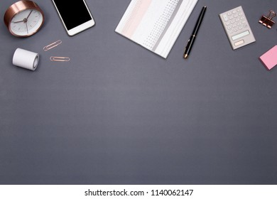 Office table desk with smartphone and other office supplies on grey background. Top view with copy space, flat lay.