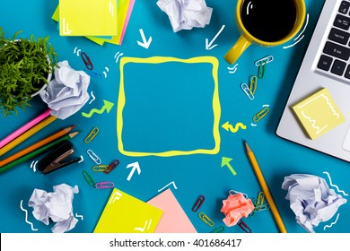 Office table desk with supplies, white blank note pad, cup, pen, pc, crumpled paper, flower on blue background. Top view