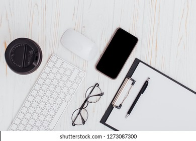 Office table with keyboard and mouse, blank with glasses and pen, headphones and photocamera, coffee cup on isolated white background.