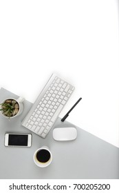 Office table with  keyboard, mouse, and smartphone on modern two tone (white and grey) background.