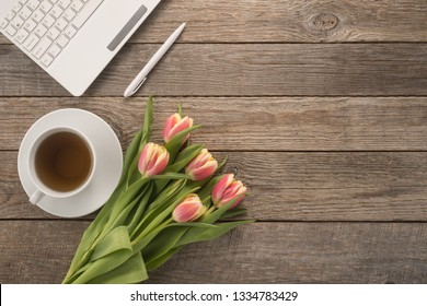 Office table with  keyboard, pen, cup of tea and flowers