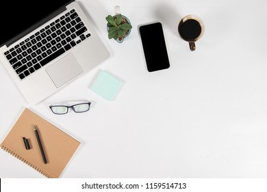 Office table with laptop computer, smartphone, pen, notebook and coffee on isolated pure white background / Laptop and tablet mockup concept. (Selective Focus)