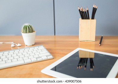 Office table with laptop and pencils.