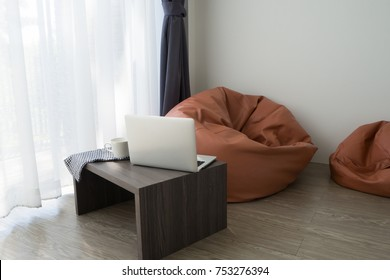 Office table with laptop, white coffee cup and orange beab bag on white curtain windows texture background in living room.