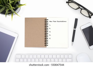 Office table with new year resolutions concept with open notebook, pen, mobile phone, tablet, small plant and eye glasses on white desk