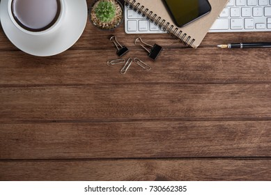 Office table with notebook, computer keyboard, mouse, cup of coffee, tablet pc and smartphone, Top view with copy space on wooden floor