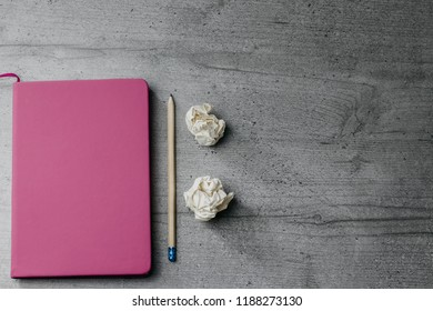 Office table with notebook, pencil and  crumpled papers. Top view image