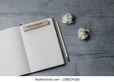 Office table with notebook, pencil, crumpled papers, wooden sign ' November'. Top view image