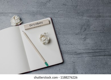 Office table with notebook, pencil, crumpled papers, wooden sign 'October'. Top view image. Copy space
