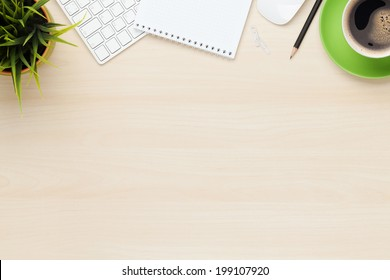 Office table with notepad, computer and coffee cup. View from above with copy space - Shutterstock ID 199107920