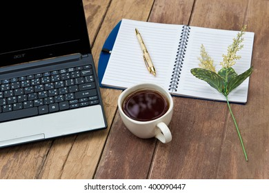 Office table with notepad, computer and coffee cup. View from above.