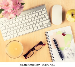 Office table with notepad, computer, reading glasses and healthy breakfast. View from above with copy space