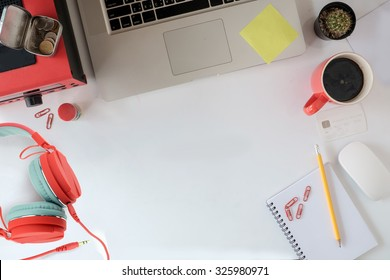 Office table with notepad, laptop and coffee cup above view shot