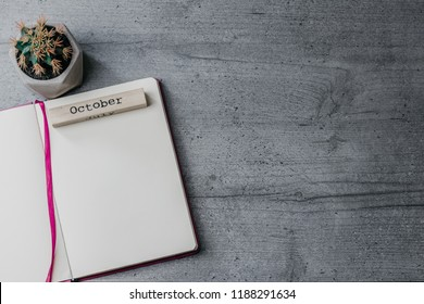Office table with opened notebook, cactus and wooden sign ' October'. Top view image, copy space