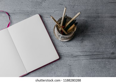 Office table with pencils and opened notebook. Top view image, copy space