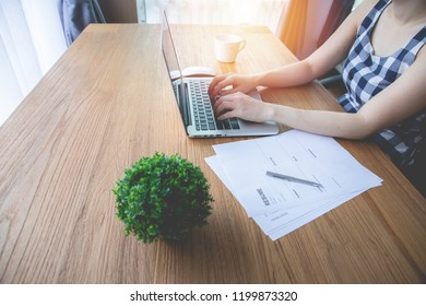 office table with resume paper information and young asian woman using laptop for find job with online internet. side view table.