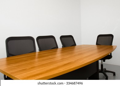office table in small white room with chairs