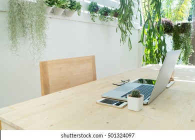 office table and wood chair with notebook, tablet, coffee cup and cactus flower on pot at tree garden background, Natural office for working at home, Tree garden with office table, Work place at home.