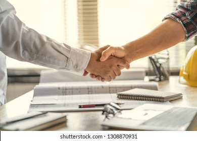Office teamwork is happy and shake hands to celebrate in success of finish in job planning about home building construction project
