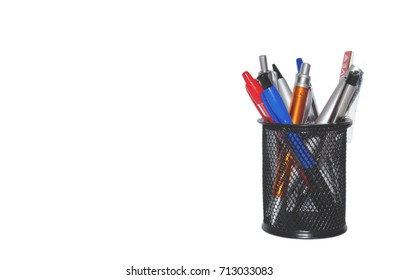 Office tool - color pens in a black basket isolated on white background. Copy space for text. Starting school.