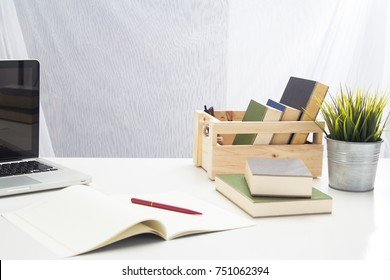 The office tool for work ,laptop,paper work, book and pen ,they are put beside tree pot on office desk,white sartin curtain background.