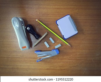 office tools of pencil, rubber stamp, and other useful secretary items on wooden floor.