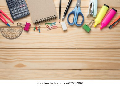 Office tools and stationery supplies on wooden table.Top view, space for text.