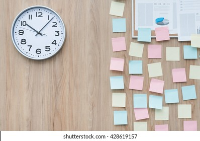 Office wall partially covered with colorful stick memo notes and a clock, ideas and deadlines concept