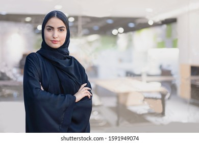 Office Woman - Arab girl on Abaya Hijab black dress in Middle East. Beautiful Arabic Emirati lady at inside a business boardroom. Portrait of Arabian female