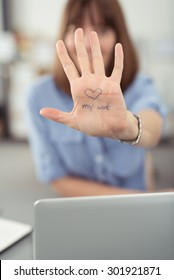 Office Woman at her Desk Showing her Bare Palm with Love My Work Concept at the Camera