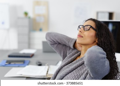 office woman leaning back, relaxing with her hands behind her neck