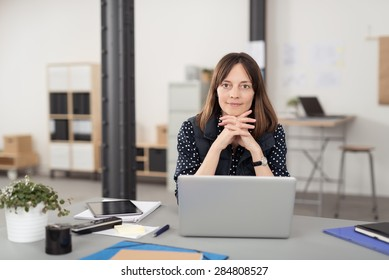 Office Woman Sitting at her Desk with Laptop Computer, Leaning on her Hands in Crossed While Smiling at the Camera.