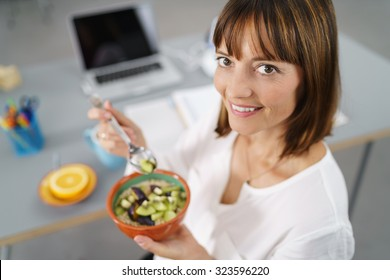 Office Woman Sitting at her Desk, Smiles at the Camera While Holding her Healthy Meal in a Bowl.