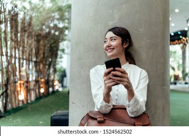 Bürofrau, mit weißem Hemd und grauem Hose, sitzend und mit dem Handy.