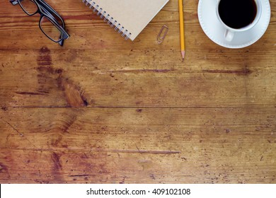 Office wooden desk with coffee, notebook and glasses. View from above with copy space.