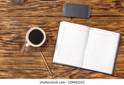 Office wooden desk with notepad, smartphone, pen and cup of coffee. Business concept.