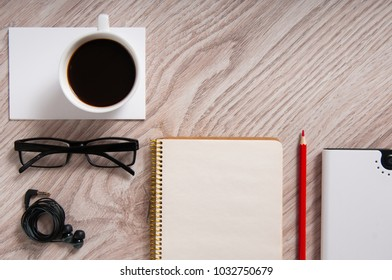 Office wooden table with coffee cup, blank notepad and supplies. Flat lay.