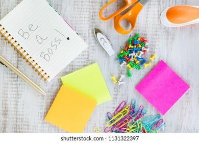 Office work supplies including notebook, jump drive, scissors, stapler, pen, post it notes, push pins, paper clips