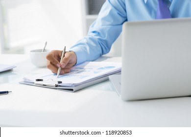 Office worker analyzing financial statistics to develop business plan