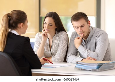 Office worker attending and showing contract trying to convince to a suspicious couple sitting in a desk at office