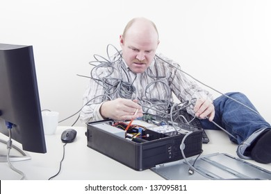 Office Worker with Computer Problems. Office worker / businessman in cables has  computer problems.