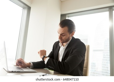 Office worker at desk looking at wristwatch, waiting for the end of work day. Busy young entrepreneur hurrying to finish computer report. Businessman checks time remaining to important office meeting