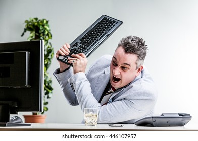 office worker destroying his computer by smashing the keyboard over the screen