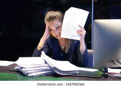 Office worker is distressed with a lot of paperwork in front of her. A lot of paper work in office. Yelling and screaming for bad results. Businesswoman in problems.