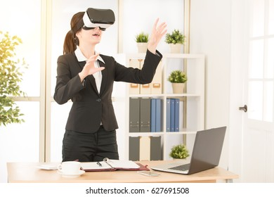 office worker doing business at office studio with vr headset device showing report in the air moving information with hands. mixed race asian chinese model.